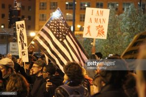 WASHINGTON, DC - NOVEMBER 25: Protesters hold banners during a march through the streets at the second night of protests after the Ferguson Grand Jury decision about white Officer Daren Wilson that he will not be faced with criminal charges for the shooting death of black 18-year old Michael Brown in Ferguson, on November 25, 2014 in Washington, United States. (Photo by Michael Hernandez/Anadolu Agency/Getty Images)
